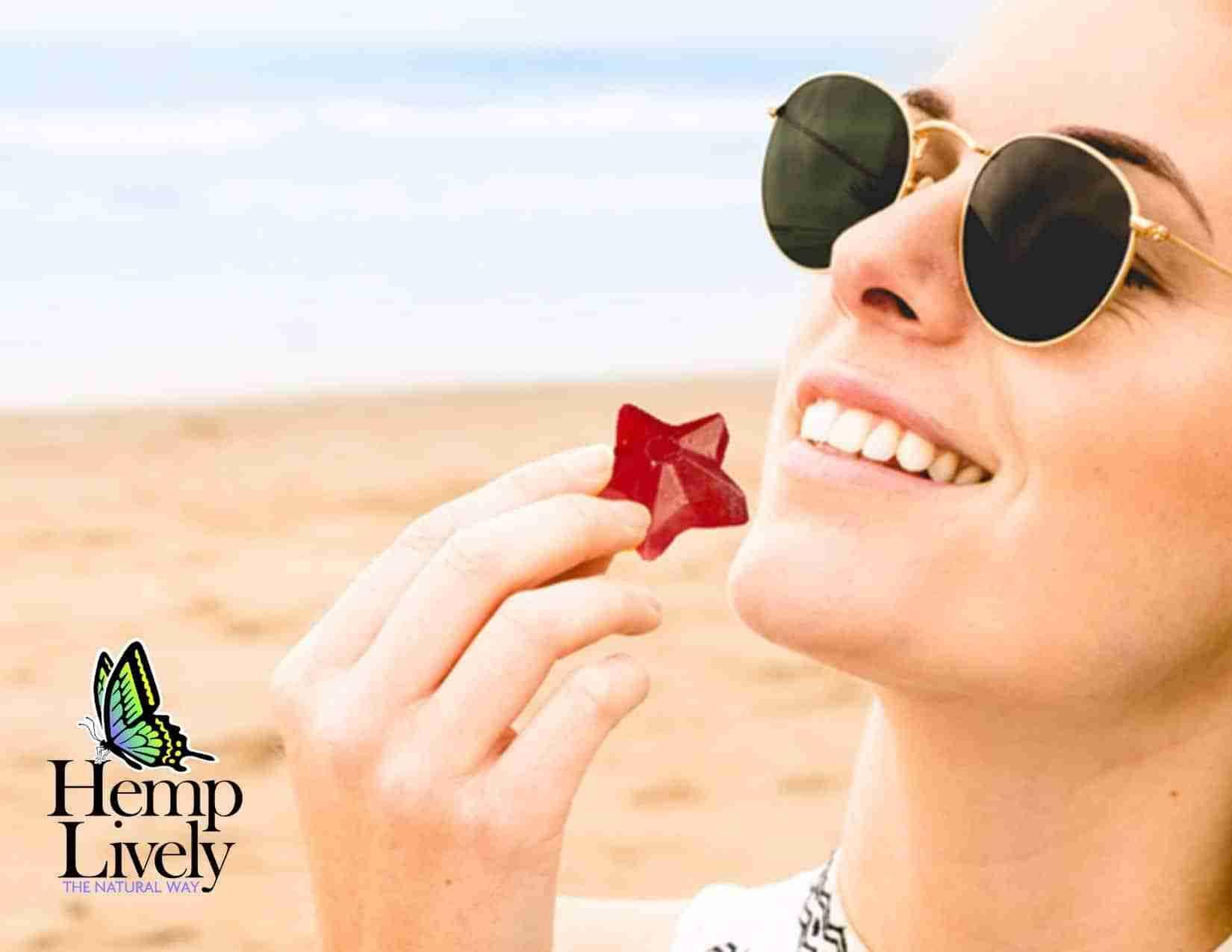 woman eating a hemp lively gummy on the beach